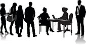 A vector silhouette illustration of business people.  A group of young adults stand and wait to see a young women who is sitting at a desk using her lap top.  A man in a business suit stands to the right and observes.