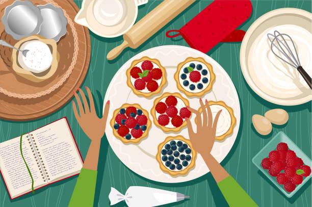 Making tartlets Female hands decorating raspberry and blueberry tartlets. decorating a cake stock illustrations
