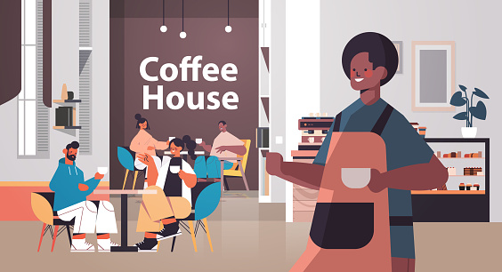 male barista in uniform working in coffee house waiter in apron serving coffee for clients