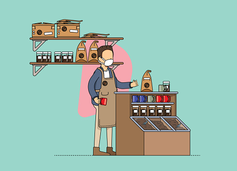 Male fair trade coffee store owner, preparation of an order for delivery. Adjusting to the new normal and social distancing norms, wearing mask at work.