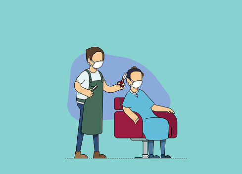 Male hairdresser and client at a hair salon, discussing and cutting hair. Adjusting to the new normal and social distancing norms, wearing mask at work.