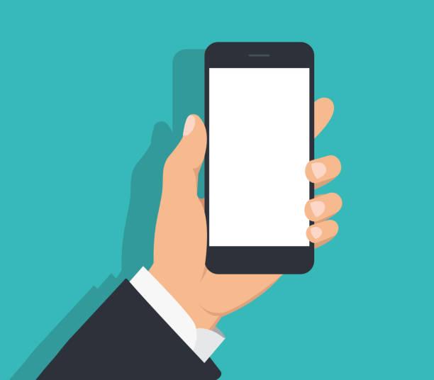 męska ręka w czarnym garniturze trzymająca smartfon z białym pustym ekranem. ręka z telefonem komórkowym z cieniem na zielonym tle. - ręka człowieka stock illustrations