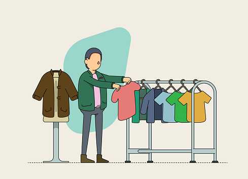 Male second hand clothing store owner checking inventory. Sustainable retailing and product up cycling.