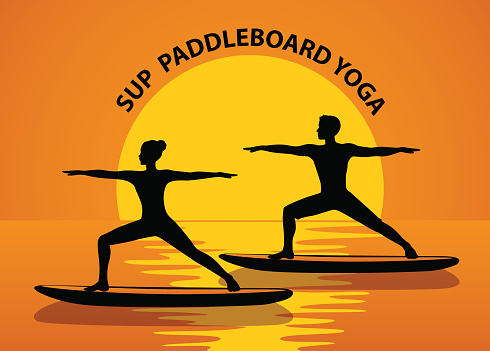 Man and woman doing stand up paddleboard yoga on boards, silhouettes at sunset