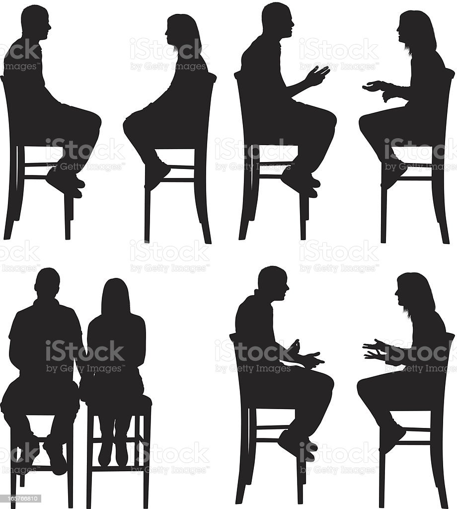 Man And Women Sitting On Stools Facing Each Other Stock