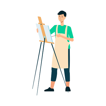 A man brunet painter and artist in an apron draws with a brush at the easel.