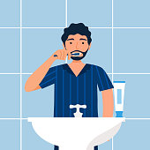 Man brushing teeth in the bathroom in flat design. Guy cleaning teeth to prevent tooth decay. Dental care.