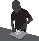 Vector silhouette of a man chopping vegetables on a cutting board with a knife.