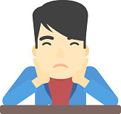 An asian man sitting at the table and clutching his head vector flat design illustration isolated on white background.