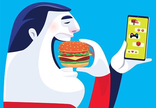 man eating hamburger and checking smartphone