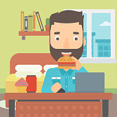 A hipster man with the beard working on laptop while eating junk food on the background of bedroom vector flat design illustration. Square layout.