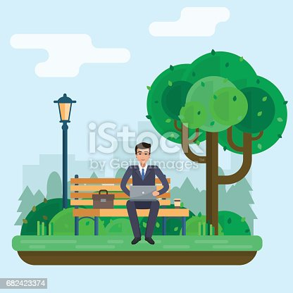 istock Man freelancer works in park with computer on bench under tree. 682423374