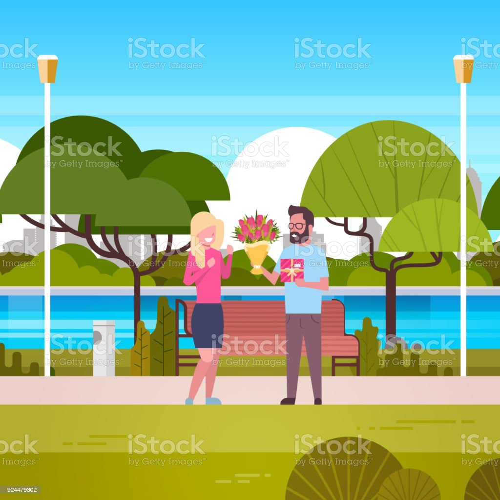man give girl gift and bouquet over green park background