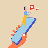 istock Man holding like button with mobile phone 1335462145