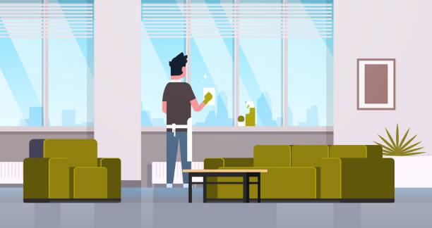 mann in handschuhen und schürze reinigung fenster mit lappen sauberer spray hinterblicht kerl, die hausarbeit konzept moderne wohnung wohnzimmer in der wohnung in voller länge horizontal - fenster putzen stock-grafiken, -clipart, -cartoons und -symbole