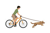 A man on a bike walking with a dog.