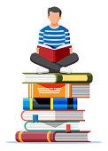 Man sitting cross-legged on stack of books