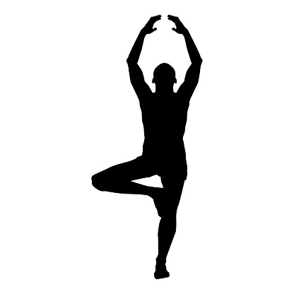 man stands in the lotus position doing yoga silhouette