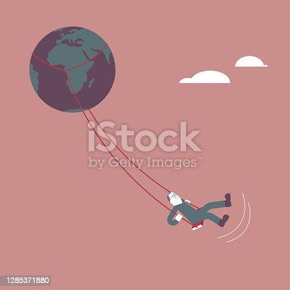 istock A man swings on an globe. 1285371880