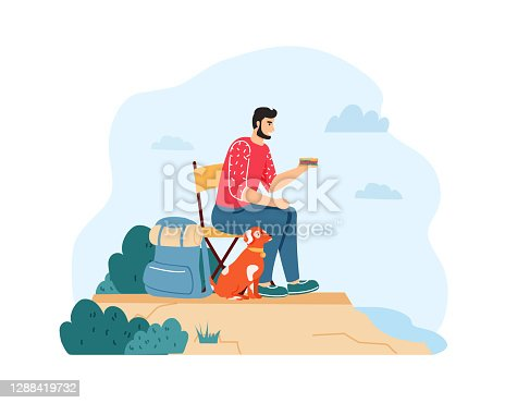 istock Man with dog hiking and having summer trip. Guy sitting on chair and eating sandwich near backpack on cliff 1288419732