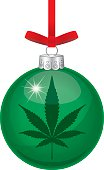 Vector illustration of a shiny green glass christmas ornament with a marijuana leaf on it hanging from a red ribbon.