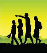 A family enjoy a walk in the country. All silhouettes are in full including feet.
