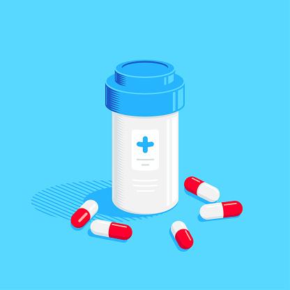 Medicine bottle and pills on blue background.