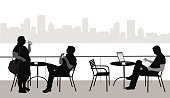 A vector silhouette illustration of young men and women at a water front cafe accross from a city scape.