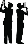 Vector silhouette of two men taking pictures with their digital tablets.