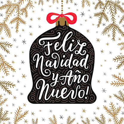 Merry Christmas and Happy New Year hand drawn lettering phrases in Spanish language on the bell toy with red bow. Spruce branches background.