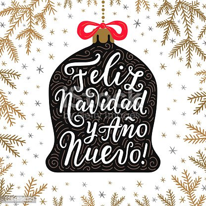 istock Merry Christmas and Happy New Year hand drawn lettering phrases in Spanish language on the bell toy with red bow. Spruce branches background. 1284898321