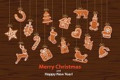 Merry Christmas and Happy New Year seasonal winter hanging rope garland with gingerbread cookies on wooden texture