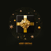 Black gift box and stars Merry Christmas and New Year greeting card design.  Black and gold color composition. Vector illustration. Elements are layered separately in vector file.