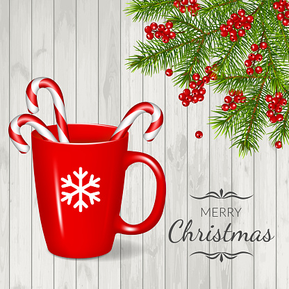 Merry Christmas greeting card with fir branches, red cup and candy cane, isolated on wood background.