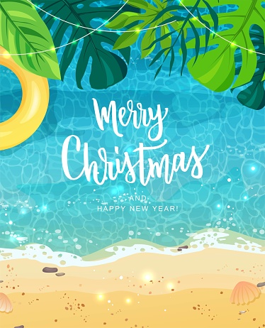 Merry Christmas hand lettering text for exotic New Year celebration. Summer seashore with sand and yellow swim ring, tropical leaves, top view. The wave rolls onto the sand, sea foam, blue water.
