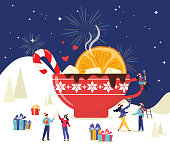 Merry Christmas. Winter scene with a large mug of cocoa and tiny people, men and women having fun in the snow and celebrating the winter holidays. Friendly business team at a corporate party.