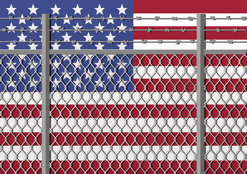 Metal fence with barbed wire on a USA flag. Separation concept, borders protection. Template for march against anti-immigration policies. Social issues on refugees or illegal immigrants.