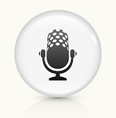 Microphone Icon on simple white round button. This 100% royalty free vector button is circular in shape and the icon is the primary subject of the composition. There is a slight reflection visible at the bottom.