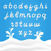 Milk font with Latin letters. White milk hand drawn alphabet with liquid letters on background with milk splashes