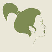 Minimalistic portrait of a girl in profile with hair gathered on the crown of her head with makeup on a color background