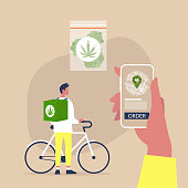 Mobile application for online cannabis delivery service, Young male courier with a large backpack riding a bike