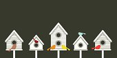 A row of modern-styled birdhouses with their multi-colored bird occupants perched on top of them like a friendly neighborhood