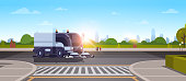 modern city street sweeper truck washing asphalt on crossroad industrial vehicle cleaning machine urban road service concept cityscape sunset background flat horizontal vector illustration