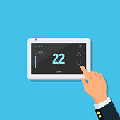 Modern digital touchscreen thermostat. Close-up of person hand with temperature controller.