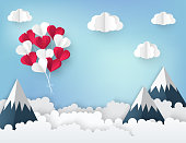 Modern paper art origami background. Bunch of red and white paper heart balloons, fluffy clouds, high mountains and place for text. Valentine's day, wedding invitation