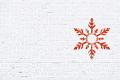 A white, light gray colored brick wall with rectangular blocks, textured grungy backgrounds. No text. No people, copy space, copyspace. Vector Xmas background. White colour vintage wall paper with an Xmas snow flake to the right in empty grunge the frame. Simple design in red and white colors.