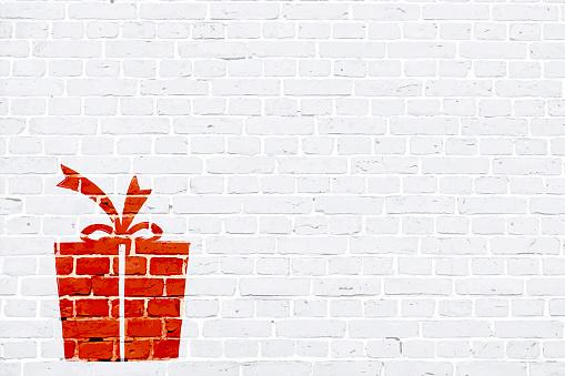 Moderno color blanco color ladrillo patrón de pared textura grunge fondo de Navidad ilustración vectorial con una caja de regalo de Navidad de color rojo atado con un arco de cinta, graffiti graffitied en la pared