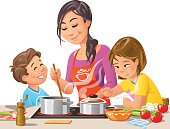 Mother with two children cooking and preparing meal in the kitchen together.