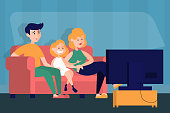 Mother, father and daughter watch TV at the home. Family on the sofa in living room. Home interior. Kid and parent lifestyle.