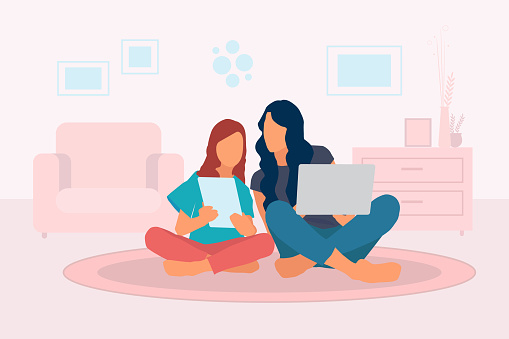 Mother teaching her daughter at home in living room, learning with laptop and digital tablet